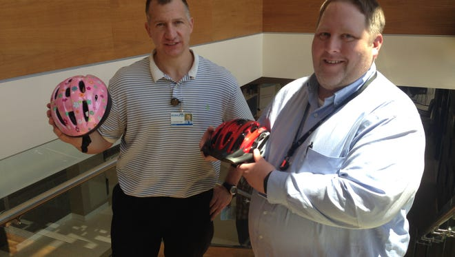 Dr. John Cegielski, left, and Borgess Health Park Director Eric Niedzwiecki show off the helmets that will be free for kids at June 19's Bike Rodeo.
