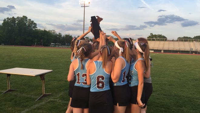 The Okemos girls lacrosse team celebrates with the regional championship trophy after an 18-6 win over DeWitt on Friday, June 2.