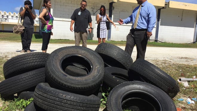 Education Superintendent Jon Fernandez and other education officials look at piles of discarded school equipment and supplies during a walkthrough of George Washington High School Thursday morning, to assess needed summer repairs.