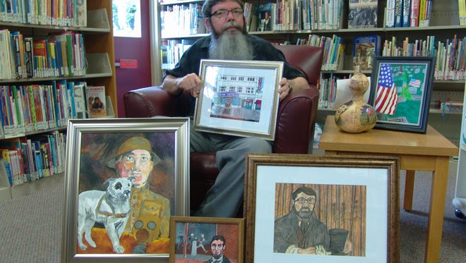 Ron Cummings is surrounded by a sample of his artwork, which is on display this month at the West Lafayette Library.