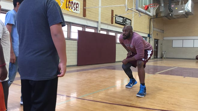 Former NFL player Michael Montgomery teaches students how to read clues in the defensive line before the ball is hiked in E Merle Smith Middle School's gym, Friday June 9, 2017. Those lessons were then applied to techniques to improve reading.