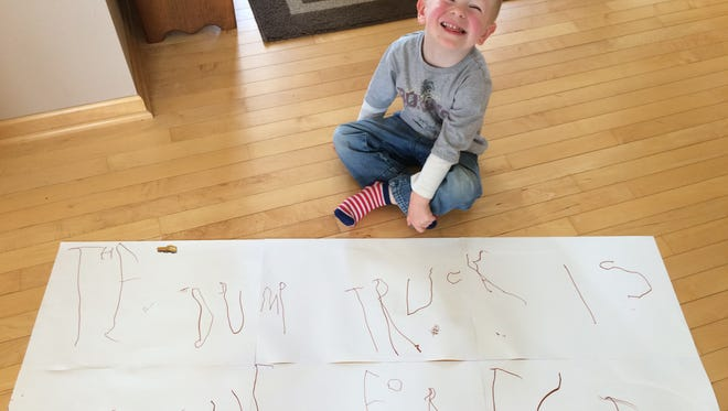 Walter Kanzenbach, 4, sits in front of a writing assignment, showing dump trucks in the forest.