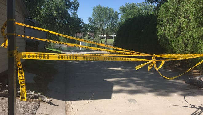 Police tape stretched across the driveway of a home on Riverside Drive where Carlsbad Police say a car driven by 19-year-old Thiessen Lambert entered the river. Lambert's body was later recovered by the Carlsbad Dive Team.