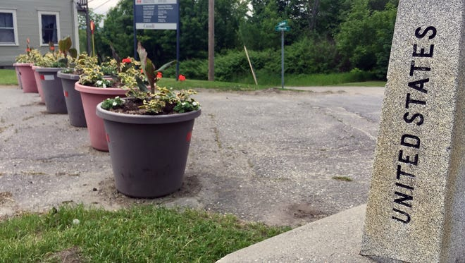 A granite marker marks the border between the United States and Canada in Derby Line, Vt., while a line of flower pots stops people from driving across the border on a road that used to connect the two countries.