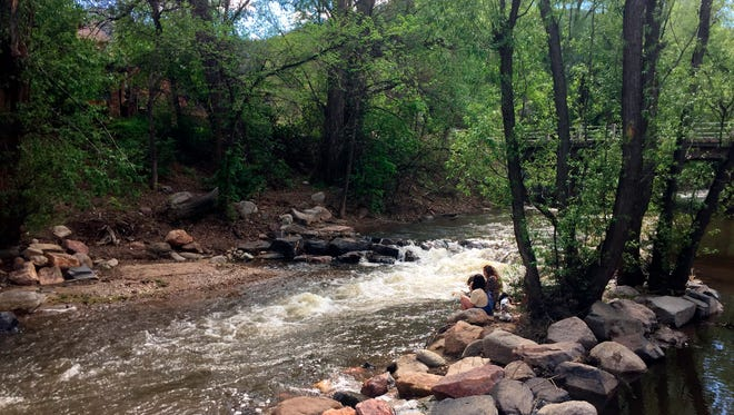 This May 13, 2017, photo shows people relaxing along Boulder Creek in Boulder, Colo.
