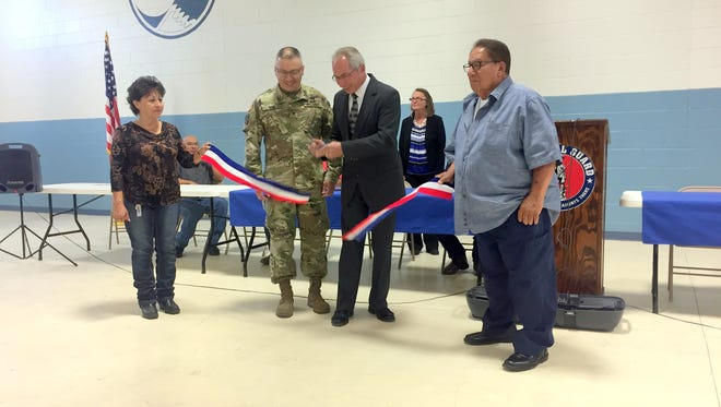 Trustee Olga Amador, left, holds the ribbon along with Trustee Richard Esparza during a ceremony held Thursday morning at the National Guard Armory in Santa Clara. Brigadadier General Kenneth Nava stands next to Mayor Richard Bauch as he cuts the ribbon.
