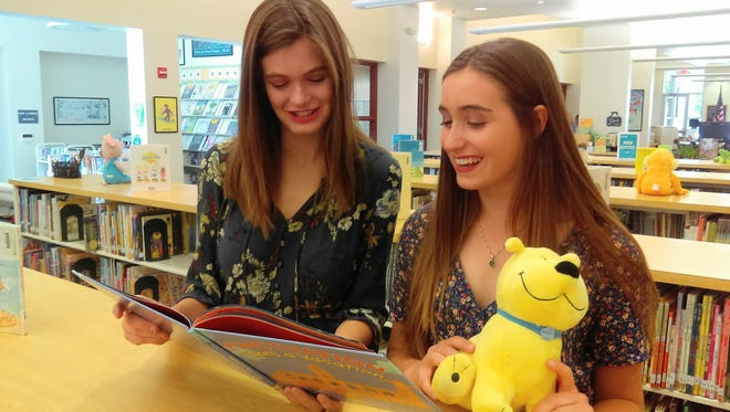 Sisters Claire and Sophia Stetson couldn't wait to see what new books were available when they visited their old haunt, the Visalia Unified Learning Center, to take a picture for this story. They came away with a stack of books to read.