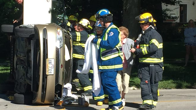 Rescue personnel extract an elderly woman from a vehicle that rolled over on Rawson Avenue Tuesday.