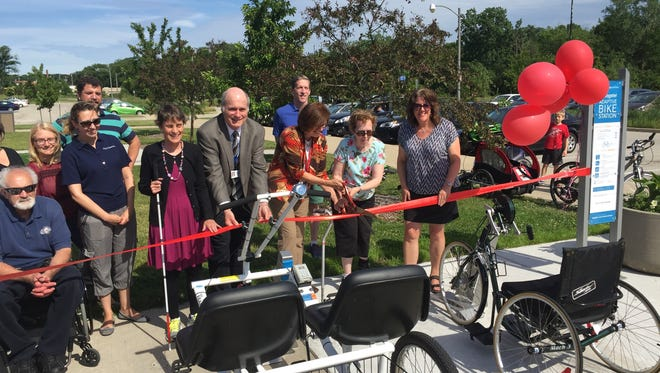 Wauwatosa Mayor Kathy Ehley cuts the ribbon on the adaptive bike sharing station in Hart Park, 7300 Chestnut St. Also in attendance and key players in bringing the bikes are Deb Palec (right) and Alderman John Dubinski (fifth from right).