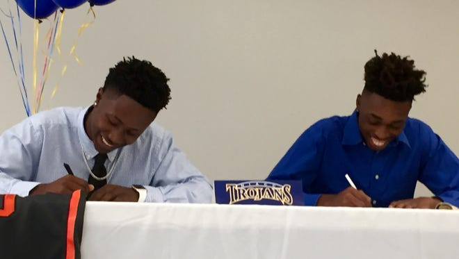 Lely graduate Rugde Hyppolite, left, and St. John Neumann grad Hollis Hardwick, right, put the pen to the paper at a signing ceremony Wednesday night at the Village School in North Naples. Both players signed with North Iowa Area Community College in Mason City, Iowa.