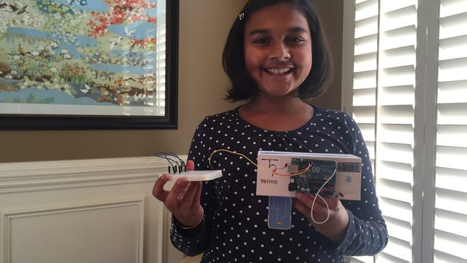 Gitanjali Rao, 11, holds her invention Tethys, a portable device that quickly detects lead in water.