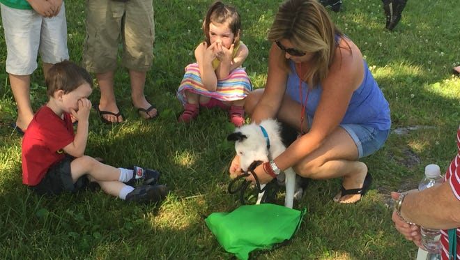 Kids gathered around Beth Riegel and her puppy, Aspen, at Tuesday's Pastoral in the Park celebration in Lexington.