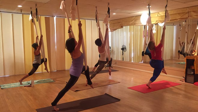 Jenn Smith, right, leads an aerial yoga practice at Yoga Bliss studio in Palm Springs.