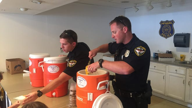 Officer Spencer (far left) and Officer Hastings hand out water ice to visiting kids Sunday.