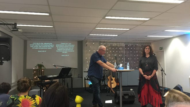Pastor Pat Hood, left, speaks at a service at LifePoint Church in Brussels, Belgium.