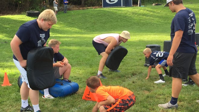 Granville varsity players Nate Miller, James Batey, Joey Rutherford and Grant Porterfield work the offensive line station Monday at the Granville Football Camp for grades 3-6.
