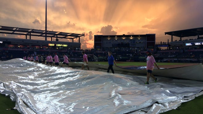 Members of the Blue Wahoos staff remove the tarp from the infield after a rain delay Thursday night July 27, 2017. Heavy rains and thunderstorms delayed Thursday night's game against Biloxi by more than an hour.