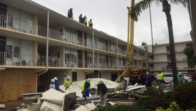 Roofers assess damage to the Outrigger Beach Resort on Monday, July 31, 2017. Guest rooms were unscathed, the resort general manager reported.