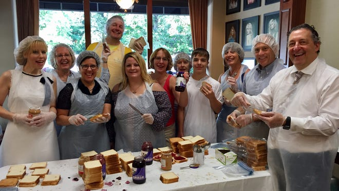 Volunteers make 500 peanut butter and jelly sandwiches at Salvatore Minardi Salon in Madison