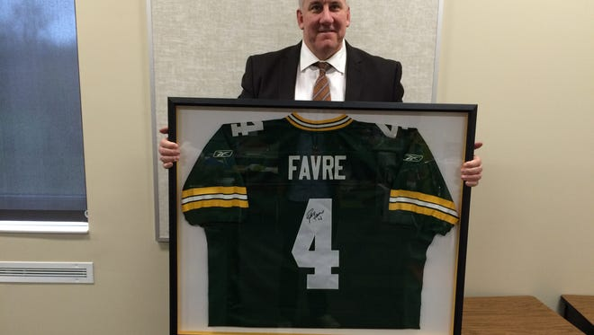 Mitchellville principal Joe Nelson holds up a signed Brett Favre jersey, one of the big ticket items for the Blue Ribbon Auction supporting Runnells and Mitchellville elementary schools.
