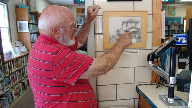 Dan Markley points to one of his photos on display at the West Lafayette Branch Library.