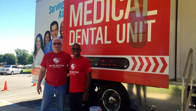 Pastor Mike Glenn, left, of Brentwood Baptist Church and Bishop Joseph Walker of Mount Zion Baptist Church, pose for a photo in front of a portable dental clinic at Hadley Park on Sat. Aug. 5. The two plan to partner on future events in an effort to heal the racial divide.