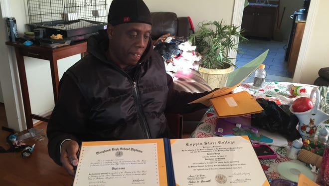 """In this Dec. 28, 2016 photo, Robert Boyd holds high school and college diplomas he earned while incarcerated, at his home in Baltimore. At 16, he was sentenced to life for his role in a home invasion that turned deadly in Baltimore. Boyd was the lookout, standing watch on the porch. The man who fired the fatal shot was acquitted at trial. By the time Boyd was released, after 34 years behind bars, even Brian Murphy, the prosecutor who tried the case in 1982, offered to testify on his behalf. """"It was not the intention of anybody back then that guys like this wouldn't get paroled,"""" Murphy said. """"It doesn't sound fair or legal."""" (AP Photo/Juliet Linderman)"""