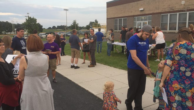 Area residents gather outside Kennard-Dale High School during a community open house held by Ohio-based power company Transource.
