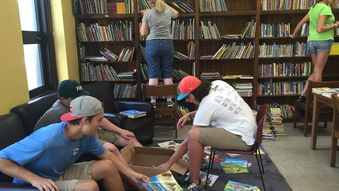 (From left) Brighton High School students Joseph Bragg, in blue, Sean Meisling, Angela Krebs, Bradford Bragg and Megan Parmeter help their friend Alea Krasiewich stock the school library at Bennett Elementary School in Detroit with donated books, in this photo taken Wednesday, July 6, 2016.