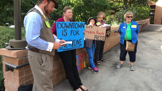 Residents protest Tuesday outside Fort Collins City Hall against new restriction on sitting and lying on sidewalks.