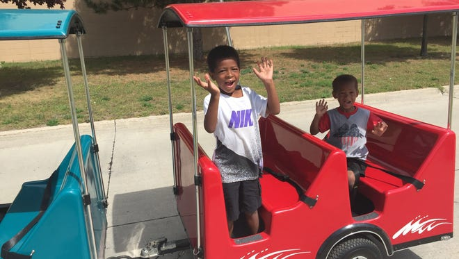 Kids wave from the back of a train during the 2017 NAACP Field Days parade.
