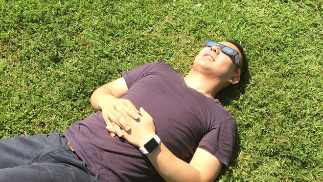 Kevin Cheng, of Maryland, relaxes and enjoys the eclipse from White House's Discover Totality event on Monday, Aug. 21.