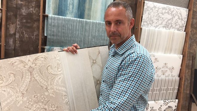 PJ Delaye, president of York Wallcoverings, holds a sample of the company's wallpaper that was installed in the White House Oval Office recently.