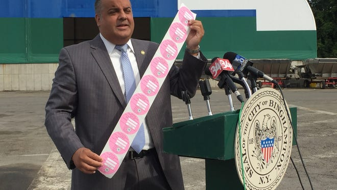 Binghamton Mayor Richard David holds up pink stickers at a press conference August 28.