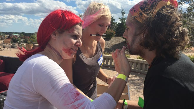 """Amy Coon (left) applies special effects makeup to Actor & Makeup Artist, Brandon Rasberry  in a timed makeup test as part of the preparation for the Franklin Halloween attraction known as """"The Hill has Eyes"""". In the background Alex Whitmarsh prepares some product to help make the horror look as realistic as possible."""