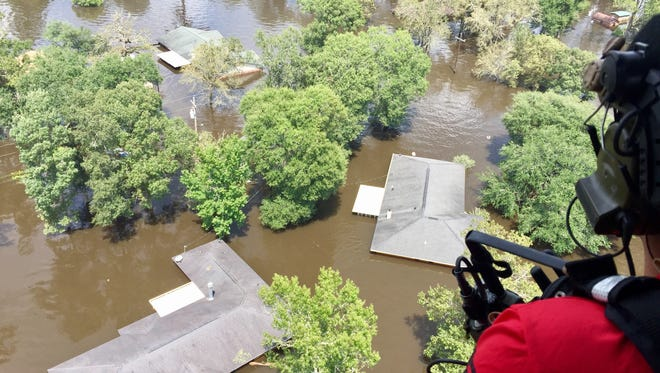 Senior Airman Josh Langley watches for storm victims amid houses that are submerged to the roofline in Bevil Oaks, Texas.