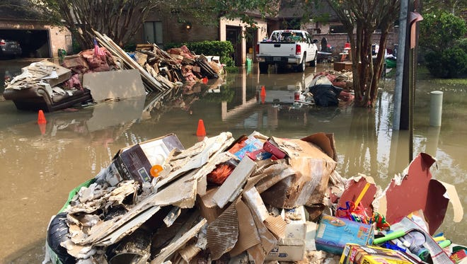 Heaps of debris sit amid Hurricane Harvey floodwaters outside a ruined house in the Memorial Drive Acres neighborhood inside Houston's mandatory evacuation zone.