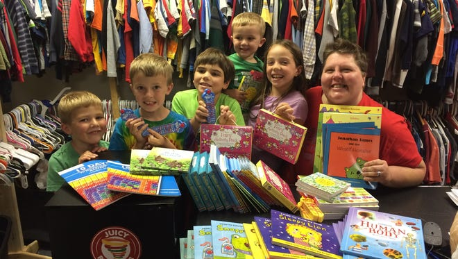 """Foster Closet manager Michele Austin (right) happily accepted the donations of books from children who read over the summer to """"Build a Better World."""""""