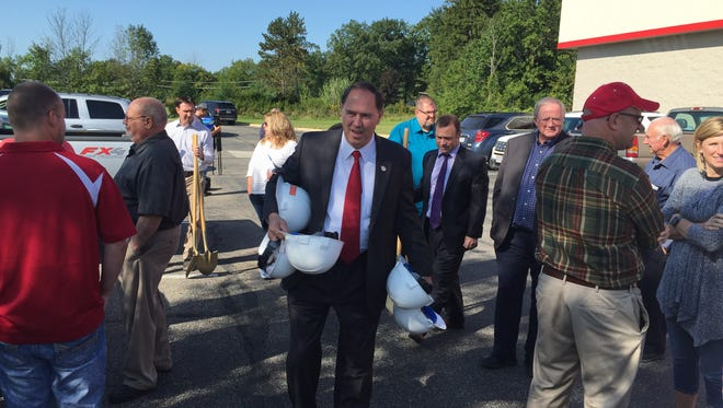 Shelby Mayor Steve Schag has his hands full of construction helmets before Wednesday's ground-breaking for a new Arby's.