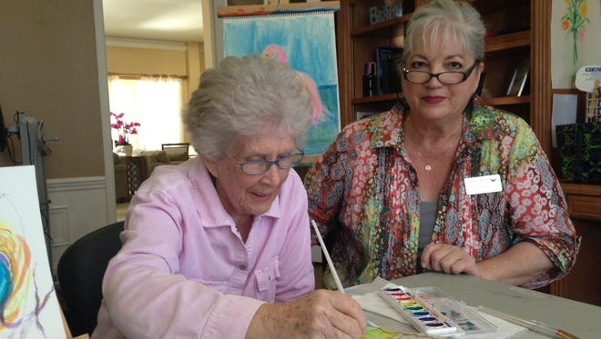 Jone Sadow, life enrichment assistant at Tequesta Terrace Assistant Living, assists resident Christine in painting with watercolors as part of its art program.