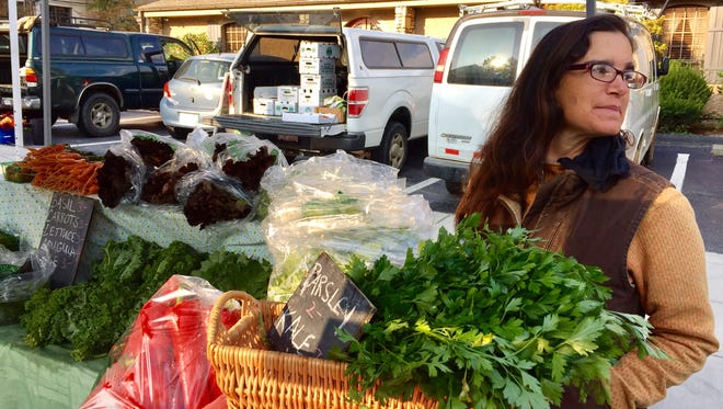 Nicole DelCogliano of Green Toe Ground sold vegetables and herbs at the Asheville City Market Saturday.