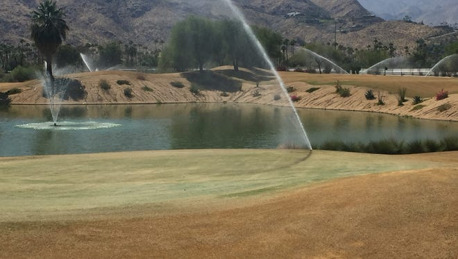 Sprinklers water the 17th hole on the Resort Course at Tahquitz Creek Golf Resort in Palm Springs. The Resort Course is one of the courses that has overseeded early this year and could be open in a few weeks.