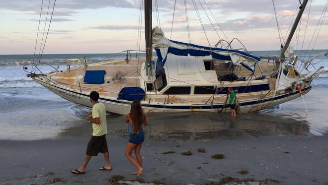 Beach-goers examine the grounded sailboat at Spessard Holland South Beach Park.