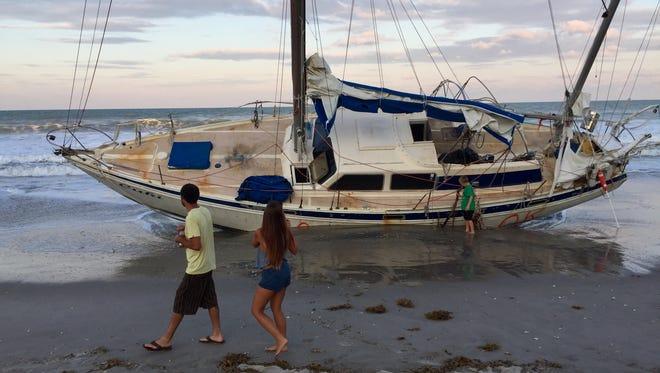 Beach-goers examine the grounded sailboat at Spessard Holland South Beach Park.