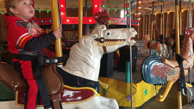 With wide eyes (soon gleeful), Draven, 3,  anticipates his first ride at the Carousel Rest Area of Shelby.