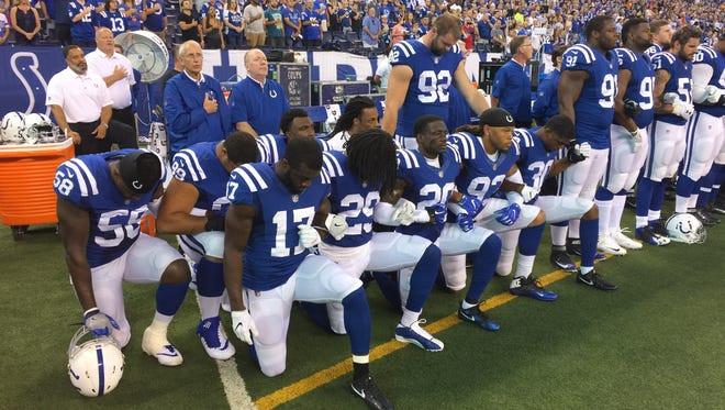 Indianapolis Colts players kneel and lock arms on the sideline before their game against the Cleveland Browns.