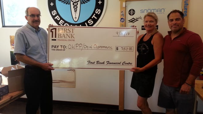Oconomowoc Watershed Protection Program Director Tom Steinbach (left) accepts a $750 donation check from Susanna (middle) and Cris Rosario, owners of Paddleboard Specialists, on Sept. 11.