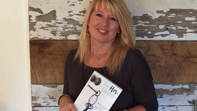 "Beth Duewel stands in front of a DIY door with a copy of her first book, ""Fix Her Upper: Hope and Laughter Through a God Renovated Life."" Rhonda Rhea is the co-author."