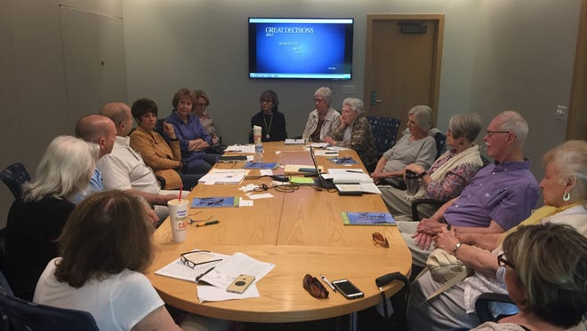 Participants in the Great Decisions group at the Howell Library discuss nuclear security on Sept. 27, 2017.