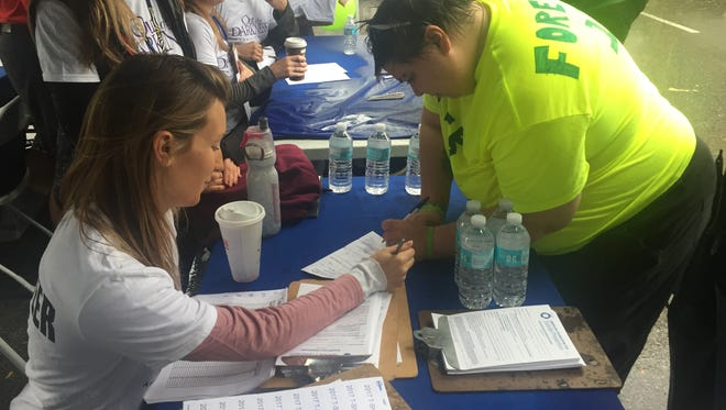 Christina Zoccoli of Connecticut, who grew up in Marlboro, left, helps Jennifer Vanbuskirk of the City of Poughkeepsie register for the American Foundation for Suicide Prevention, Hudson Valley Chapter, Out of the Darkness Walk. The walk was held Saturday at Walkway Over the Hudson in Poughkeepsie.